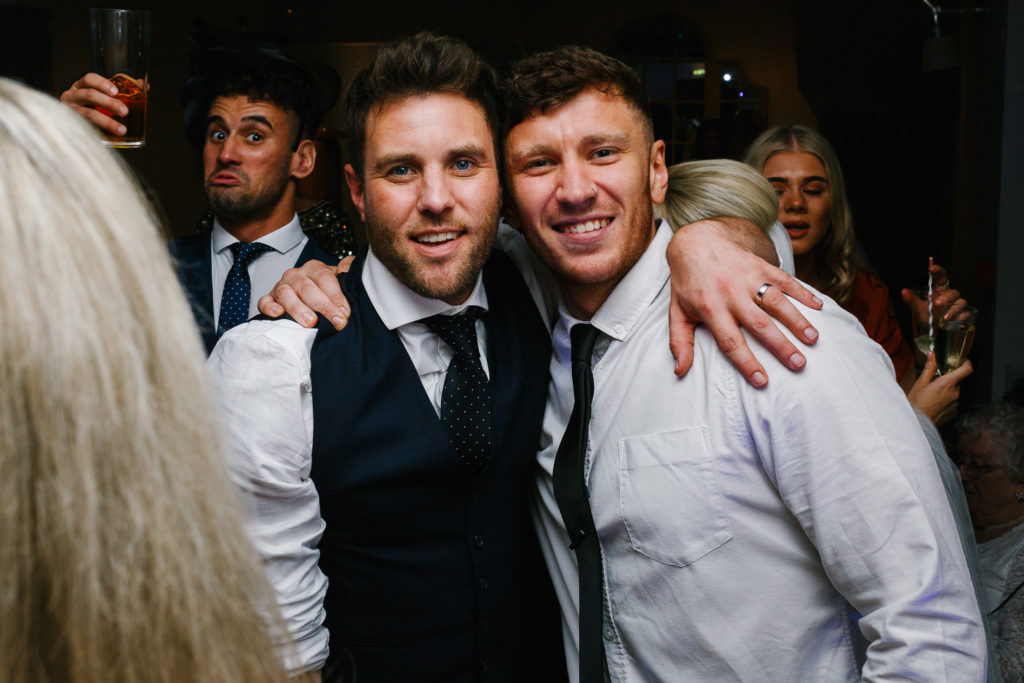 Groom with arm around best mate