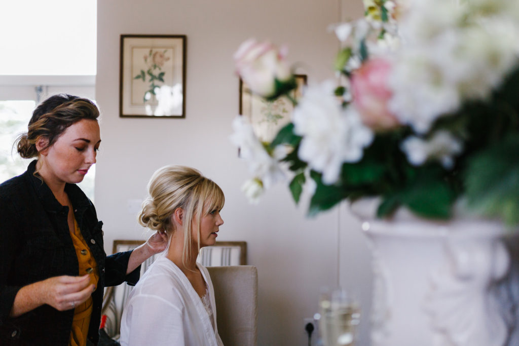 Hair dresser putting finishing touches to brides hair