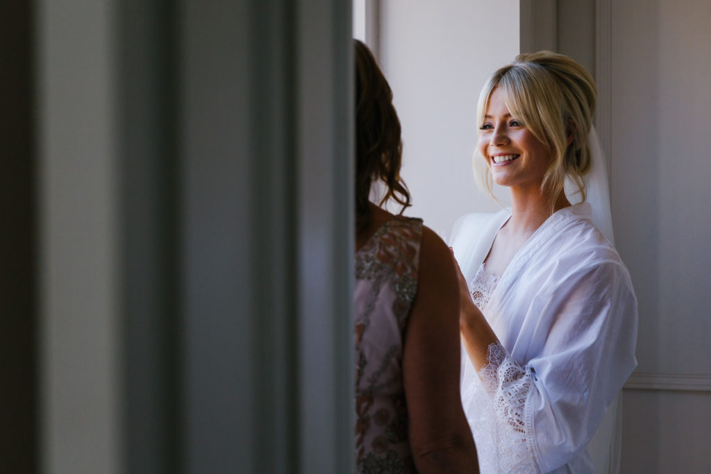 Bride chatting to bridesmaid in window