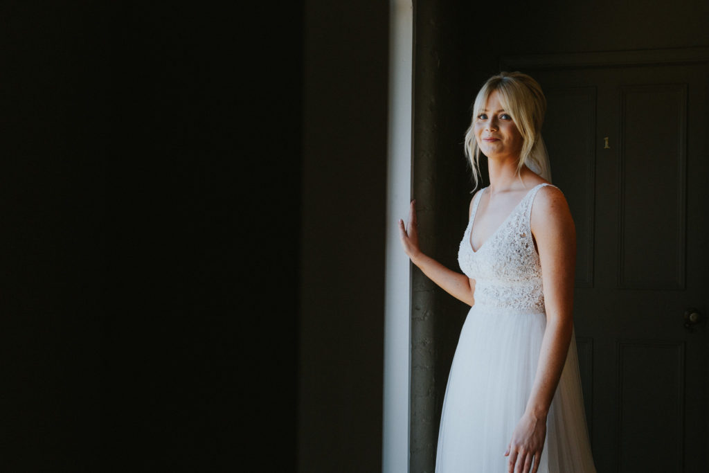 Bride stood in window smiling