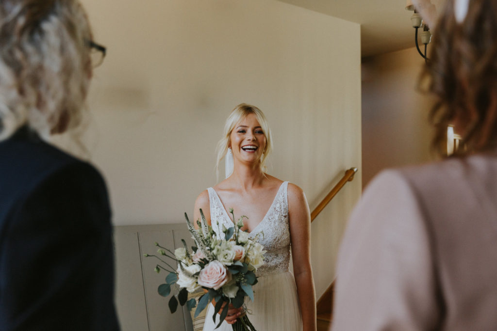 Bride showing her parents her wedding outfit in a first look