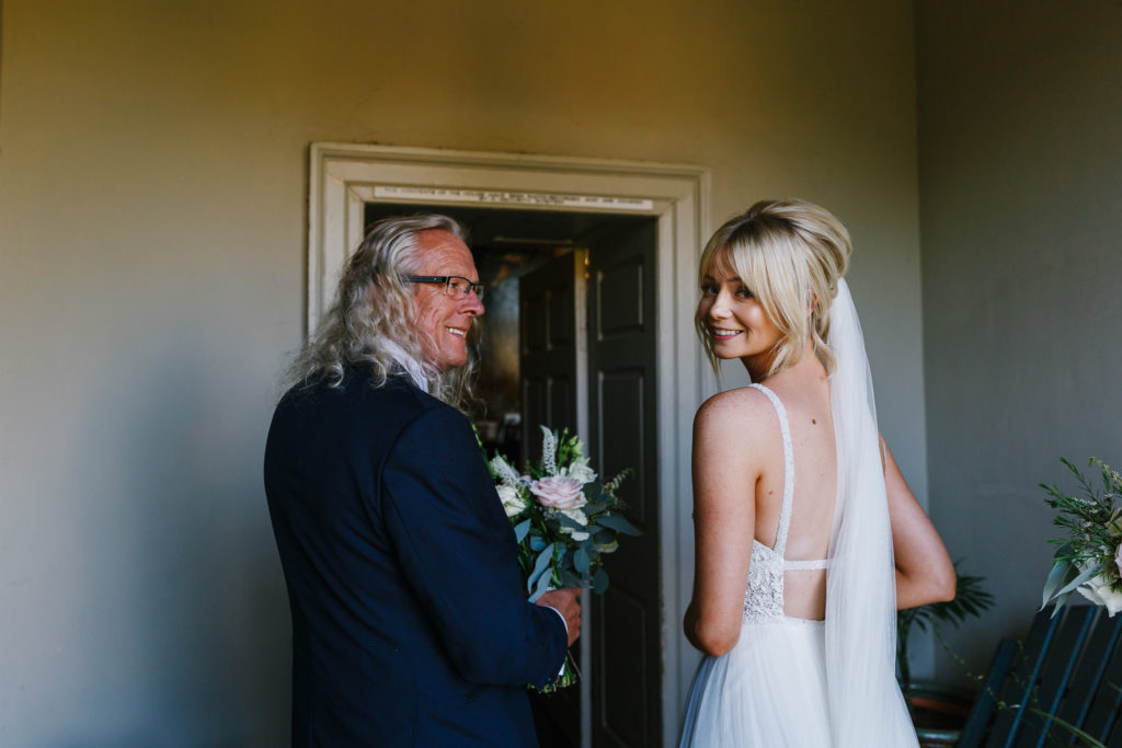 Bride looking over shoulder before entering wedding ceremony with her father