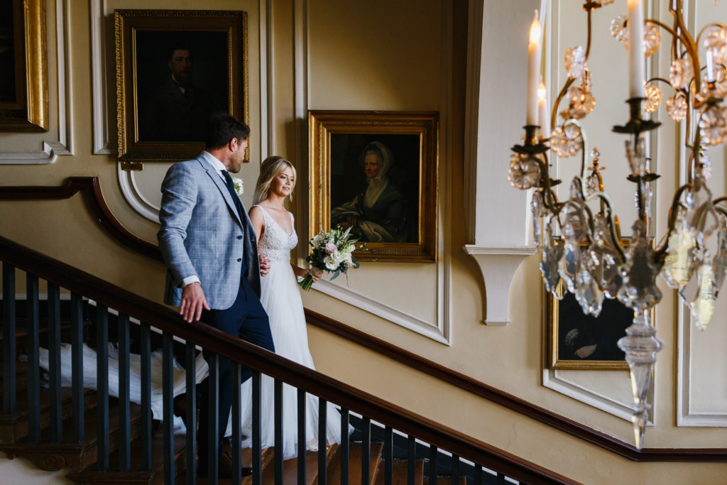 Bride & Groom walking down the stairs at Doddington Hall following their wedding ceremony
