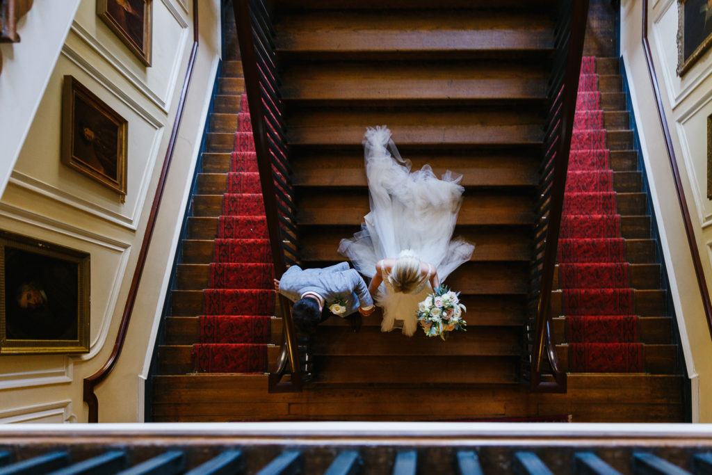 View of Bride & Groom from above on the stairs of Doddington Hall