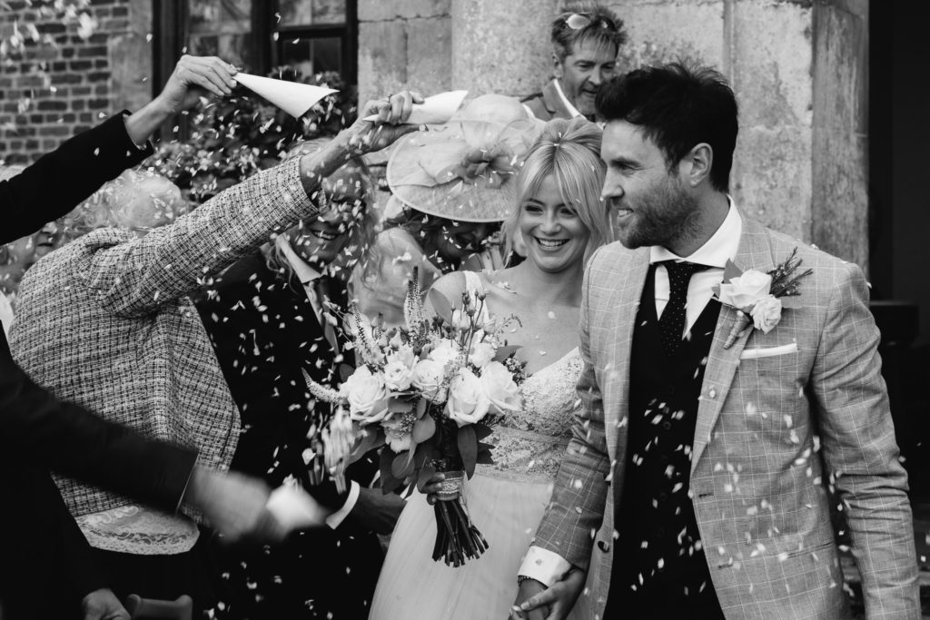 Bride & groom being showered with confetti