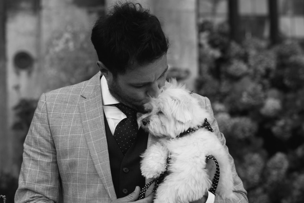 Groom kisses the head of his dog