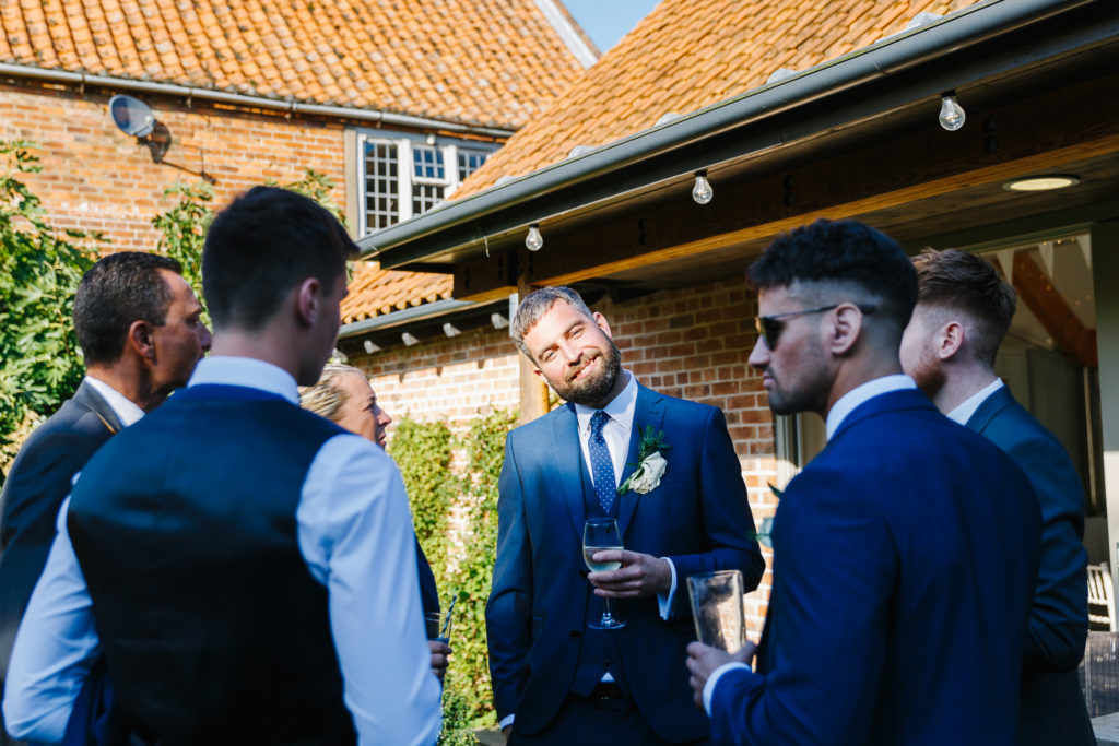 Groomsmen drinking in the walled garden