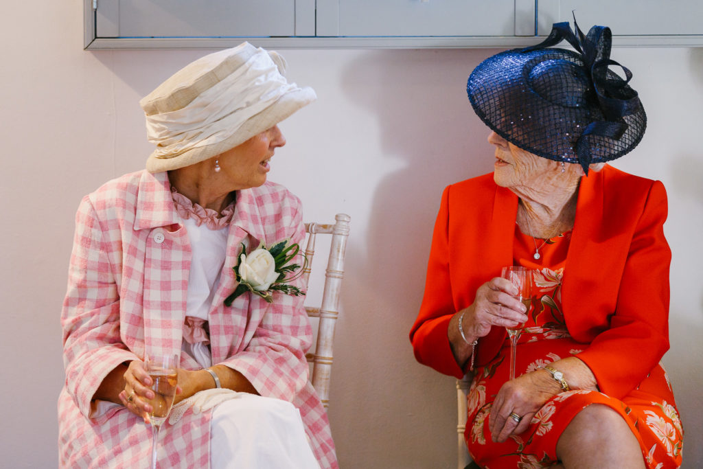 Two elderly women talking at wedding