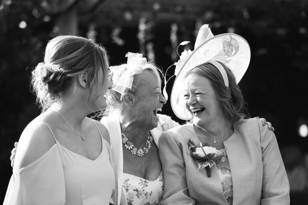 3 female wedding guests laughing