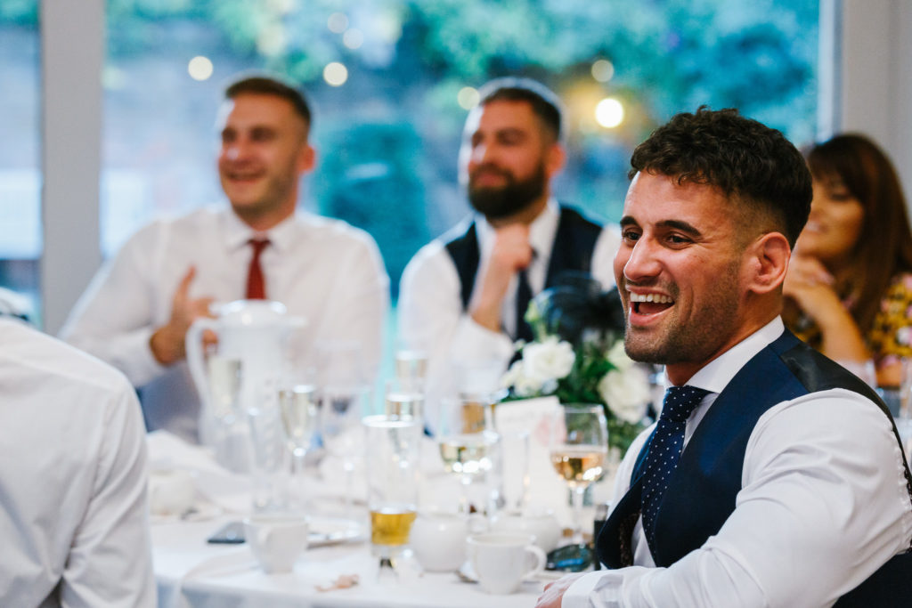 Wedding guests laughing during speech